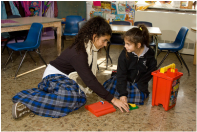 Two girls playing with blocks on the floor